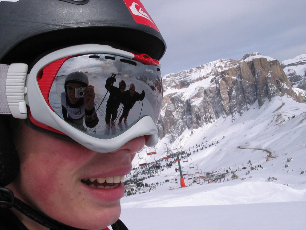 A close-up of a skier, showing his helmet and goggles