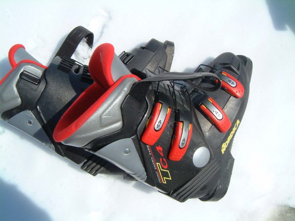 A pair of ski boots laid on the floor